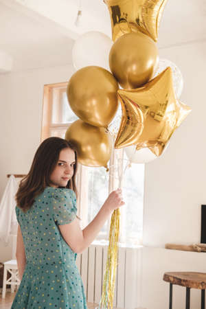 Young beautiful girl in blue dress with white polka dots celebrates her birthday and enjoys the golden balloons. Birthday alone at home during self-isolation. Reklamní fotografie - 159252490