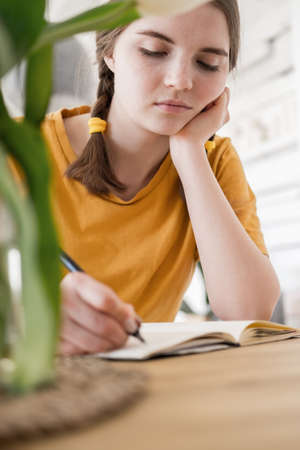 Young beautiful woman in yellow t-shirt engaged in work, online business, studying sitting at table at home. Self-isolation, study, work during quarantine, pandemic. Remote job, education, student.
