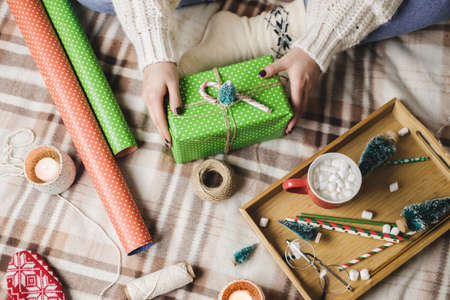Young woman sits on plaid in cozy knitted woolen white sweater, socks and wraps Christmas gift in polka dot wrapping paper. Wooden tray with mug of cocoa with marshmallows, toy tree, candle, straws. Reklamní fotografie - 159253306