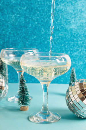 Christmas minimal festive background with disco ball, toy tree, glasses of champagne. Abstract glitter Christmas and New Year color background blue ai aqua. Bright sparkling wallpaper texture.