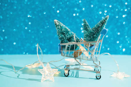 Christmas minimal festive background with star garland in supermarket basket, toy trees. Abstract Christmas and New Year color background blue ai aqua. Bright sparkling wallpaper. Stok Fotoğraf