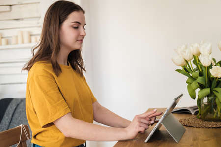 Young beautiful woman in yellow t-shirt usimg tablet for work, online business, studying sitting at home. Self-isolation, study, work during quarantine, pandemic. Remote job, education, student. 免版税图像