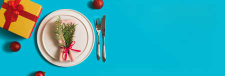 Banner with served plate and cutlery for celebration of Christmas and New Year. On plate is napkin with a Christmas tree branch, red balls. Flatlay banner on blue background with balls, gift box. Reklamní fotografie