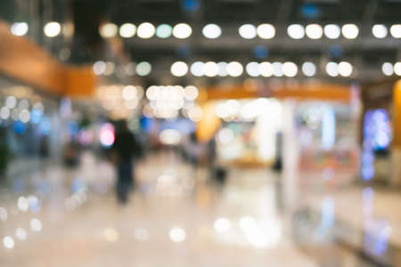 Bright defocused blurred background with unrecognizable people at the airport. Abstract image of crowd of people in public place.