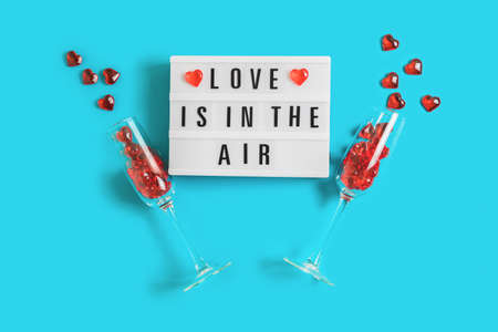 Festive background with glowing lightbox with text Love is in the Air and champagne glasses with red hearts on blue background for Valentines Day. Flatlay for 14th February. Top view.
