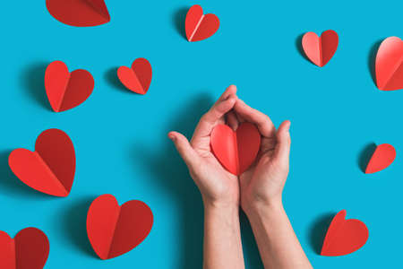 Festive background with red paper hearts for celebration of Valentines Day. Womens hands hold the heart. Flatlay by 14 February on bright blue background. Top view.