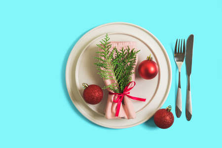 Served table with plate and cutlery for celebration of Christmas and New Year. On plate is a napkin with Christmas tree branch, red balls. Flatlay on bright blue background. Top view. 版權商用圖片