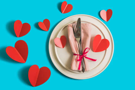 Served table with plate and cutlery forcelebration of Valentines Day. On plate is napkin with paper heart. Flatlay on bright blue background with red hearts. Top view.