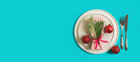 Website banner with served plate and cutlery for celebration of Christmas and New Year. On plate is a napkin with Christmas tree branch, red balls. Flatlay banner on bright blue background. Top view.