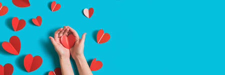 Festive banner background with red paper hearts for celebration of Valentines Day. Womens hands hold the heart. Flatlay banner by 14 February on bright blue background. Top view.
