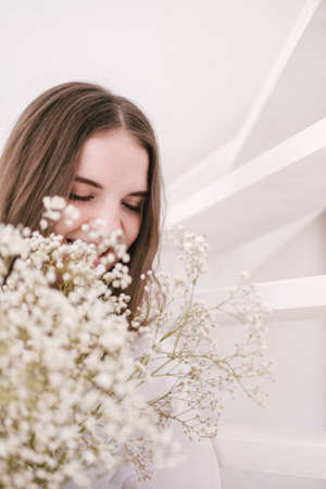 Portrait of young beautiful woman by the window with shadow from flowers on her face. Morning spring aesthetics.