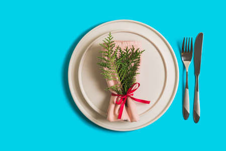 Served table with empty plate and cutlery for celebration of Christmas and New Year. On plate is napkin with Christmas tree branch. Flatlay on bright blue background. Top view.
