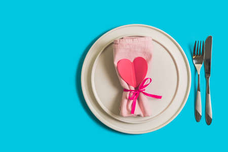 Served table with plate and cutlery for the celebration of Valentines Day. On the plate is napkin with paper heart. Flatlay on bright blue background. Top view.