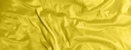 Shiny satin silk fabric with folds background texture textile. Tinted color yellow Illuminating.
