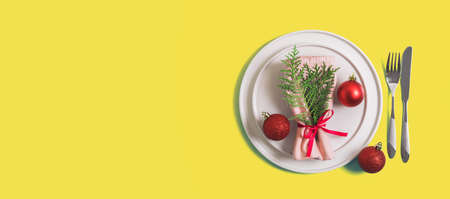Website banner with served plate and cutlery for celebration of Christmas and New Year. On plate is napkin with Christmas tree branch, red balls. Flatlay on illuminating yellow background. Top view. 版權商用圖片