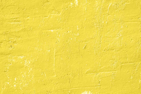 Concrete yellow colorful wall surface texture. Abstract grunge bright illuminating color background with aging effect. Copyspace.