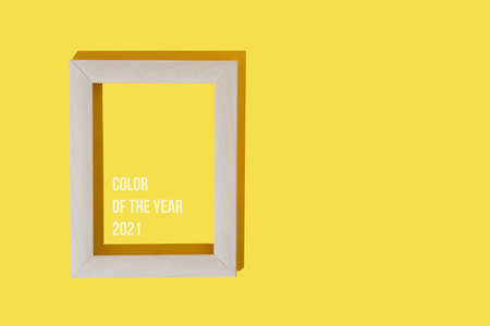 Frame for photo or painting on bright illuminating yellow background. Mockup. Place to insert text, images. Top view. Flat lay. Color of the year 2021. Reklamní fotografie