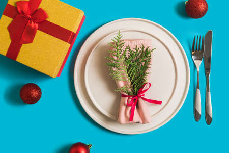 Served table with plate and cutlery for celebration of Christmas and New Year. On plate is napkin with a Christmas tree branch, red balls. Flatlay on blue background with balls, gift box. Reklamní fotografie