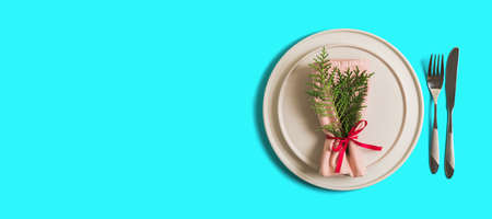 Banner with served table with empty plate and cutlery for celebration of Christmas and New Year. On plate is napkin with Christmas tree branch. Flatlay banner on bright blue background. Top view.