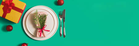 Banner with served plate and cutlery for celebration of Christmas and New Year. On plate is napkin with a Christmas tree branch, red balls. Flatlay banner on green background with balls, gift box.