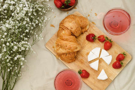 Cozy spring or summer picnic at home. Romantic picnic for Valentines Day on February 14 with croissant, strawberries, cheese and rose champagne. Protea and gypsophila flower.
