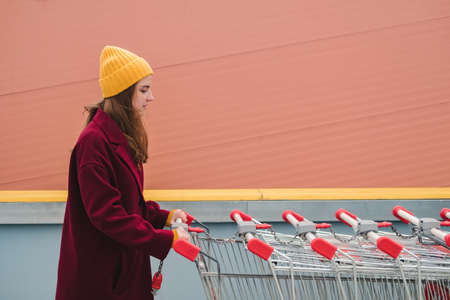 Young beautiful woman in a burgundy coat and yellow hat walks on the roof of supermarket parking lot and takes trolley.