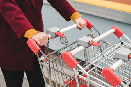 Unrecognizable person in aburgundy coat and yellow sweater walks on the roof of supermarket parking lot and takes trolley.