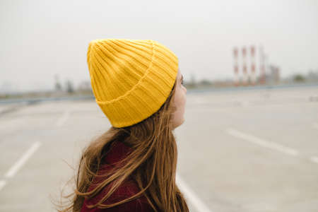 Young beautiful woman in burgundy coat and yellow hat walks along the roof of the parking lot. Loneliness, mindfulness. Reklamní fotografie