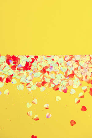 Festive Christmas and New Year background with confetti on bright yellow background. Top View. Flat lay. Concept of preparation for holidays. Reklamní fotografie