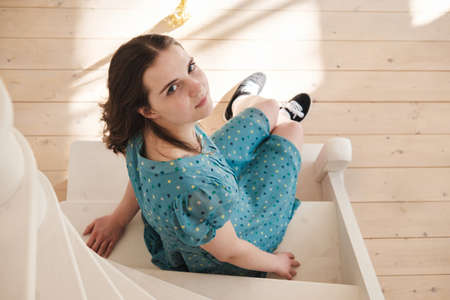 Young beautiful woman in a blue dress with polka dots sits on the stairs and looks at the camera, smiling.