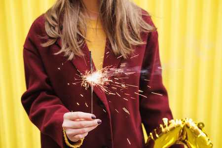 Unknown woman in burgundy coat and holding a burning sparkler in her hands against the background of bright yellow wall.