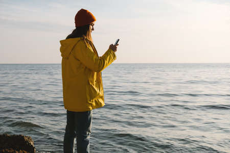 Young beautiful woman in bright yellow coat stands on the seashore or ocean and make a photo on smartphone. Concept of freedom, thoughtfulness, mindfulness.