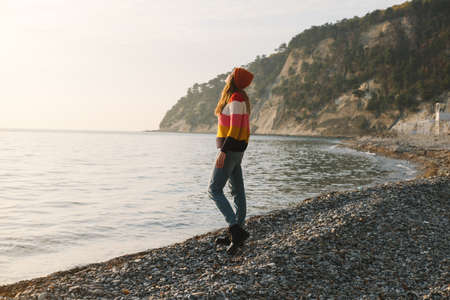 Young beautiful woman in striped sweater stands on the seashore or ocean and enjoy the view. Concept of freedom, thoughtfulness, mindfulness. Reklamní fotografie