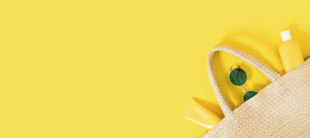 Summer yellow banner flatlay on colorful background with wicker straw bag, tubes and bottle with sunscreen, green sunglasses. Hard shadows and light. Top view. Flat lay. Trend style. Copyspace. Reklamní fotografie