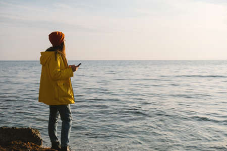 Young beautiful woman in bright yellow coat stands on the seashore or ocean with cup of tea, coffee and enjoy the view. Concept of freedom, thoughtfulness, mindfulness.