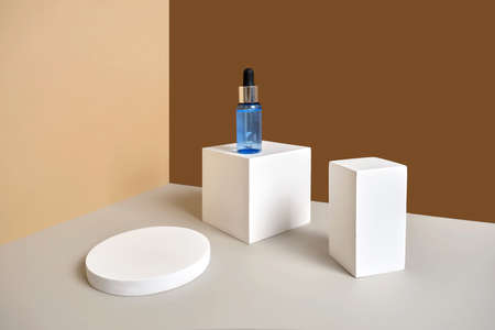 Bottle of serum stands on white round and rectangular podium with branches of dried flowers. Wabisabi style, earth tone. Skincare cosmetic composition mockup.
