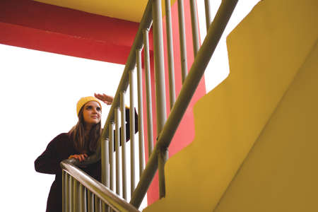 Unknown woman in burgundy coat standing on the stairs and looking up against the background of bright yellow wall.