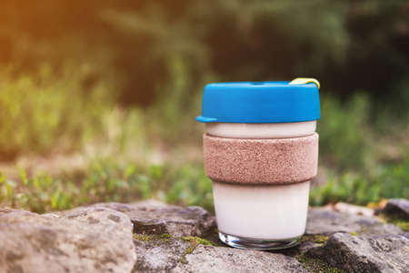 Glass cup for to-go coffee or tea with bamboo hot drink holder stands on stone outdoor. Environmental reusable mug. Conscious consumption.