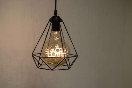 Modern loft style chandelier with a light bulb and the word love inside. Reklamní fotografie
