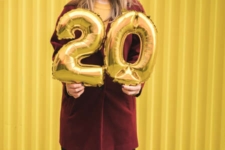 Unrecognizable woman in burgundy coat and mustard sweater holds in her hands the helium balloons of number 20 against the background of bright yellow wall. Birthday concept in twenty years. Reklamní fotografie