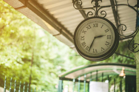 A large clock hangs at the train station in the forest. Stockfoto