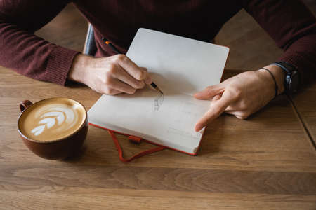 A young man sits in cafe, drinks coffee and makes notes and sketches in notebook. Stockfoto