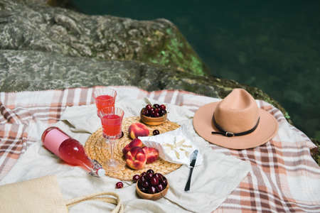 Cozy summer picnic near the lake with wine, cherry, peaches, brie cheese, camamber. Romantic picnic for Valentines Day on February 14.