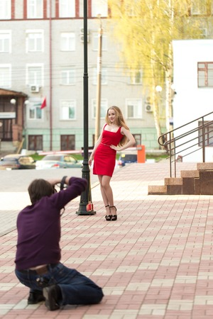 Man photographing a girl in a red dress on the street by the lamppost in Solnechny day in the summer