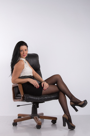 Brunette girl sits in office armchair with a pencil in hand