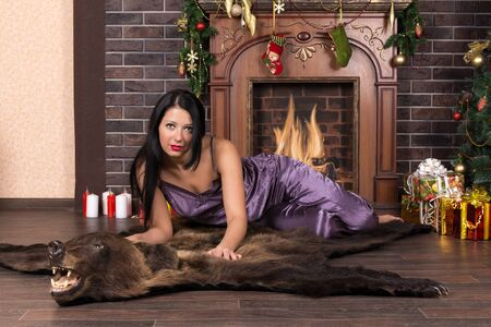 Girl in home clothes on the floor by the fireplace by the Christmas tree with gift in hand Stok Fotoğraf