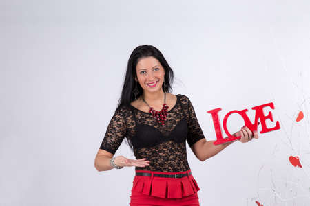 Brunette girl holding a sign with the letters of the word Love