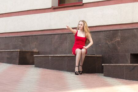 Girl in red dress sitting on the street and points his finger outstretched right hand Stok Fotoğraf