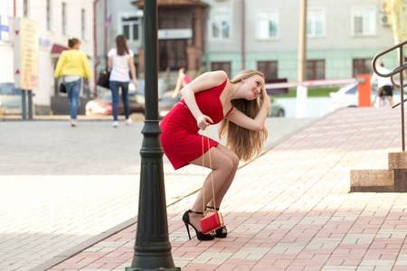 The girl in the red dress on the street adjusts her hair in the reflection in the window