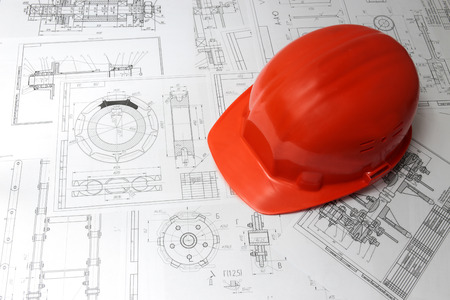 foremen: Orange protective helmet factory for engineering drawings. A must-have Accessory or attribute production engineer. Stock Photo